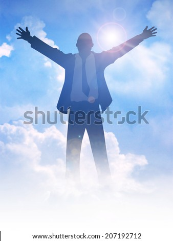 Silhouette of a man with open arms among the clouds - stock photo