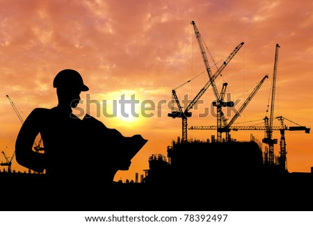 silhouette of a man working on construction site in the morning - stock photo