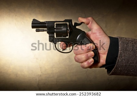 Silhouette of a mans hand with a handgun in brown - stock photo