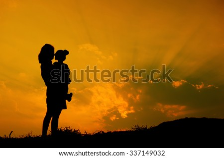 silhouette of a mother and son playing outdoors at sunset with copy space