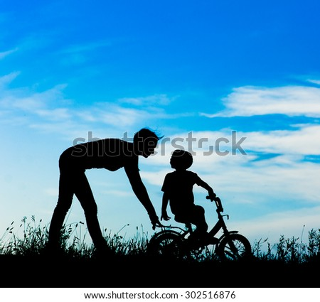 silhouette of a mother who teaches his son to ride a bike - stock photo