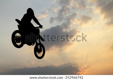 Silhouette of a motorcyclist on a background of the evening sky