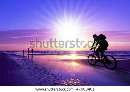 silhouette of a mountain biker on beach and sunset - stock photo