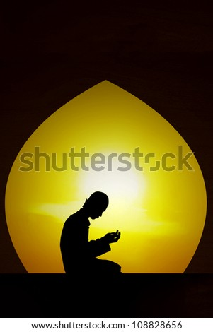 Silhouette of a muslim praying in mosque at sunset. Shot in the month of Ramadan - stock photo