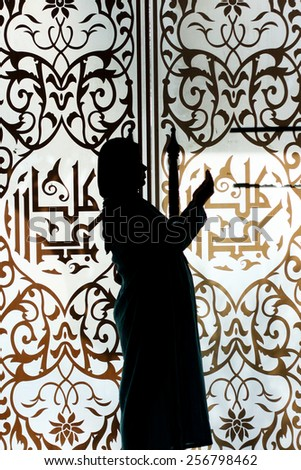 silhouette of a muslim woman praying on the arabic background - stock photo