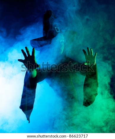 silhouette of a mysterious witch saying the spell and stretching her hands to us, with clouds of smoke around her, isolated against white background - stock photo