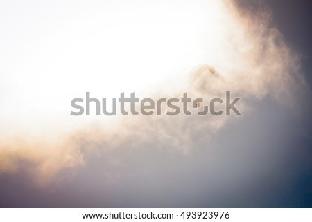 Silhouette of a paraglider flying through the clouds