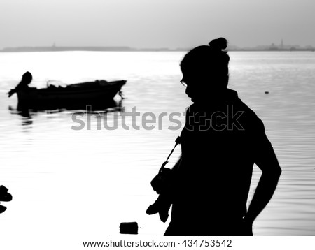 Silhouette of  a person with camera at the beach - black and white - stock photo