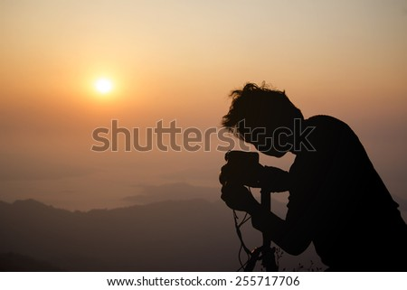 Silhouette of a photographer during the sunrise. - stock photo