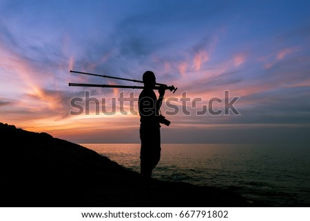 Silhouette of a photographer or traveler with tripod standing on stone ,sunset time