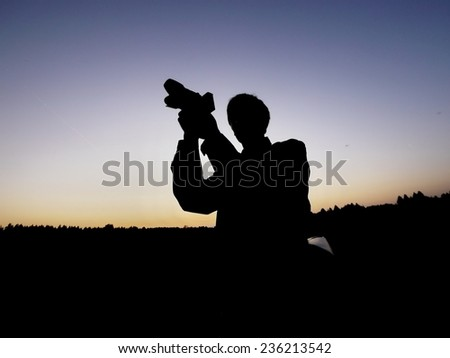 Silhouette of a photographer outdoors - stock photo