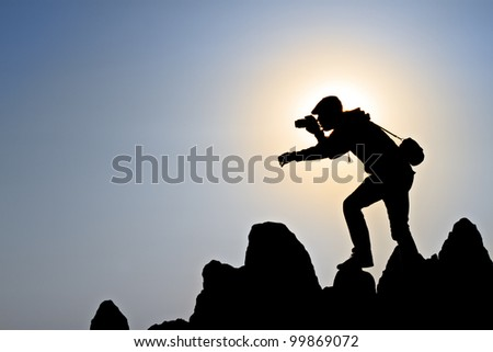 silhouette of a photographer who shoots a sunset in the mountains