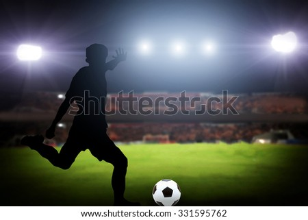 silhouette of a player shooting football on goal. Lights on the football stadium at night.