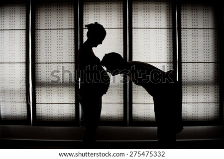 silhouette of a pregnant woman with a man - stock photo