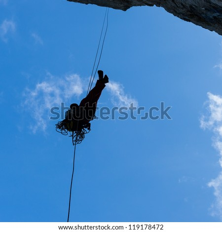 Silhouette of a rappelling man - stock photo