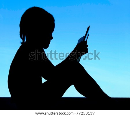 silhouette of a  reading boy at the background of sky on the window - stock photo