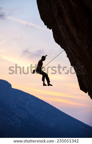 Silhouette of a rock climber falling of a cliff while lead climbing