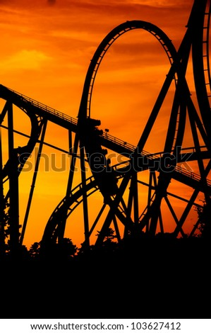 silhouette of a roller coaster at a purple sunset with people on the ride - stock photo
