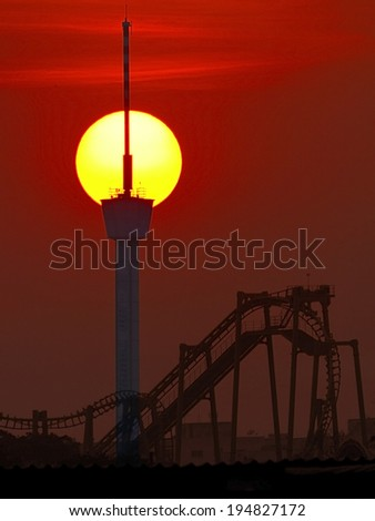 silhouette of a roller coaster at sunset, after a sunny day at entertainment park  - stock photo