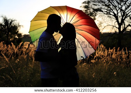 Silhouette of a romantic couple kissing in front of an umbrella. Black and white picture. Concept of love and union. - stock photo