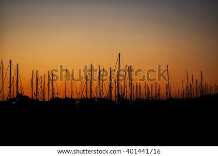 Silhouette of a row of sail masts docked at a harbor in California in the morning with a colorful orange sunrise - stock photo