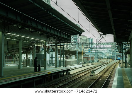 silhouette of a salary man standing alone in the train station,Business man waiting the train for go to work at platform, routine life concept