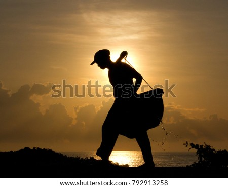 Silhouette of a salt farmer carrying homemade yoked baskets to collect sea water as part of the natural gourmet salt production process, Kasumba, Bali