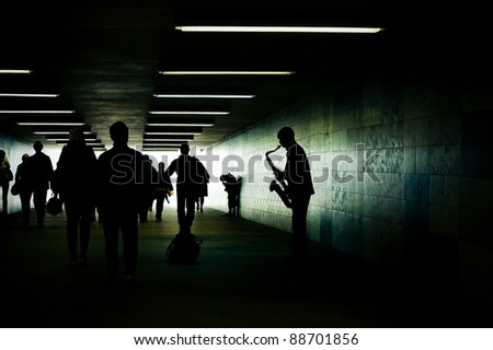 silhouette of a saxophonist in the subway tunnel