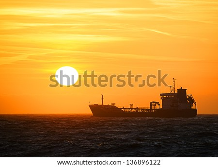 Silhouette of a ship on the north sea in front of a beautiful sunset.