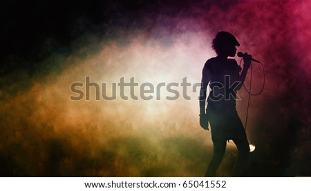 silhouette of a singing woman at a concert - stock photo