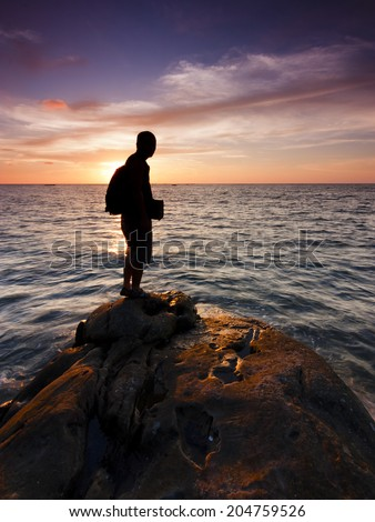 Silhouette of a single man watching the sunset - stock photo