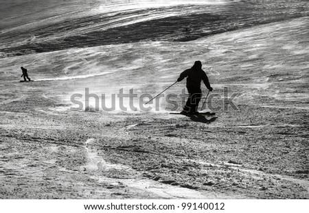Silhouette of a skiing man splashing snow while turning - stock photo