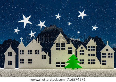 Silhouette of a small village at winter time in the night. With stars and snow in the sky