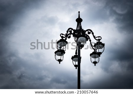 Silhouette of a street lamp with glass bulbs against dark troubled sky. External light - stock photo