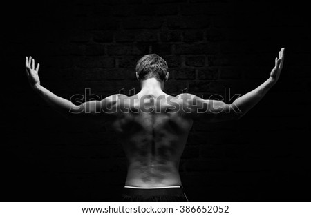 Silhouette of a strong, athletic man with dramatic light and dark background - stock photo