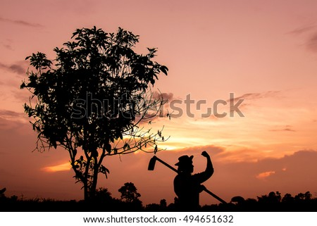 Silhouette of a strong farmer with orange golden sky. dreaming farmer background. dark tone image.
