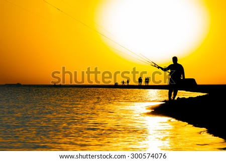 Silhouette of a surfer against the sea and picturesque orange sunset in summer evening - stock photo