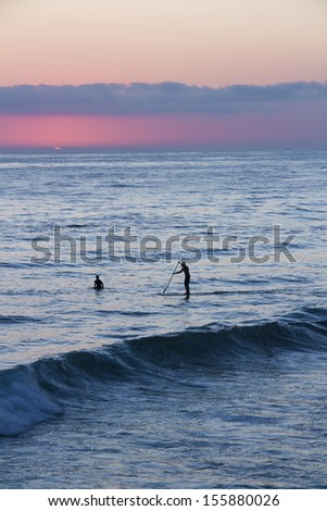 Silhouette of a surfer and paddle-boarder watching the sunset. - stock photo