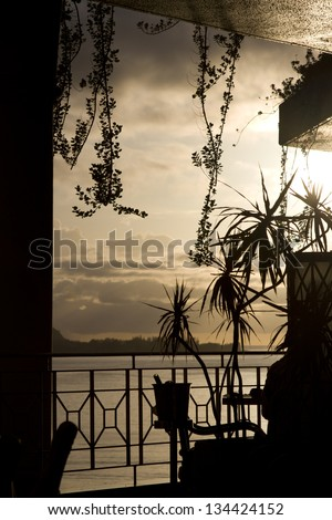 Silhouette of a table and wine bucket in a tropical location at sunset - stock photo