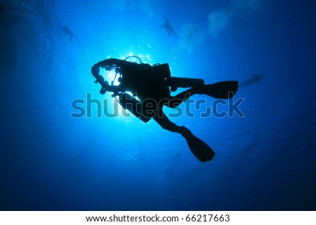 Silhouette of a Technical Scuba Diver carrying extra cylinders, returning from a deep exploration dive