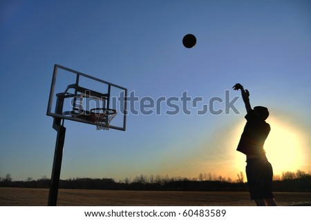 Silhouette of a Teen Boy Shooting a Basketball at Sunset, copy space - stock photo