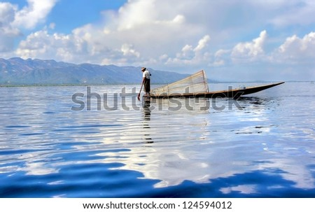 silhouette of a  traditional fishersboat on the Inle lake in Myanmar