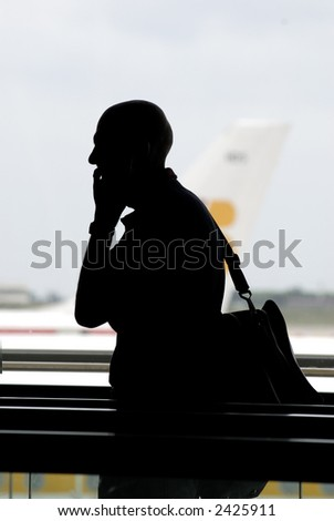 silhouette of a traveller talking by phone at barcelona airport - stock photo
