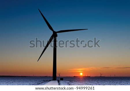 Silhouette of a wind turbine during a wintry sunset