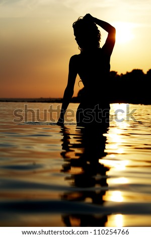 Silhouette of a woman at the beach - stock photo