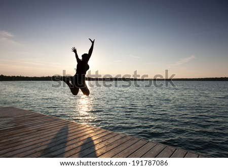 Silhouette of a woman diving in a bay, Georgian Bay, Tobermory, Ontario, Canada - stock photo