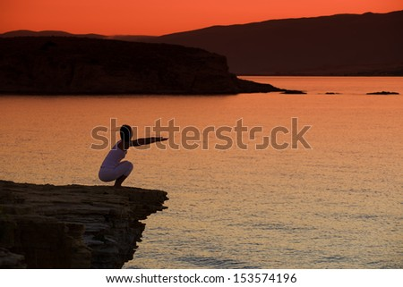Silhouette of a woman doing yoga on the beach at sunset - stock photo