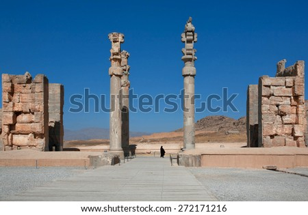 Silhouette of a woman in a Muslim hijab in between ruined columns of palace in Persepolis, modern Iran. Persepolis was a capital of the Achaemenid Empire (550 - 330 BC)