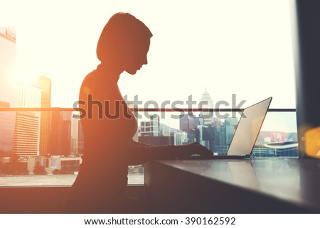 Silhouette of a woman intelligent managing director is keyboarding on laptop computer, while is sitting in modern office interior. Female economist is analyzing the activities of company via net-book - stock photo