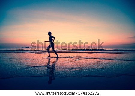 Silhouette of a woman jogger on the beach at sunset in a surreal style.